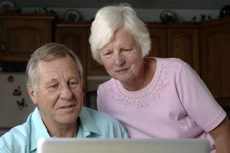 Senior romantic couple browses the Internet at their home.