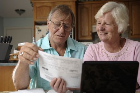 Senior romantic couple pays bills over the Internet at their home. Stock Photo - 7248793