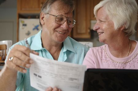 Senior romantic couple pays bills over the Internet at their home.