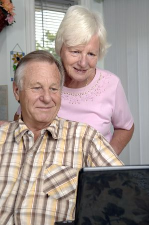 browses: Senior romantic couple browses the Internet at their home.