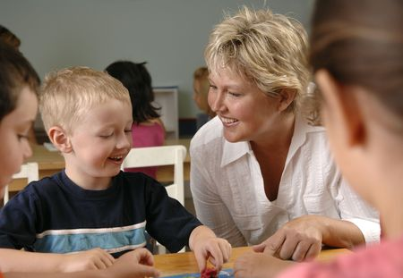 Children and teacher learn and play while playing a board-game at the preschool class. photo