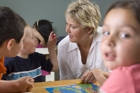 Children and teacher learn and play while playing a board-game at the preschool class.