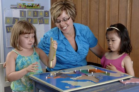 Children and teacher play and learn geography by using a puzzle map.