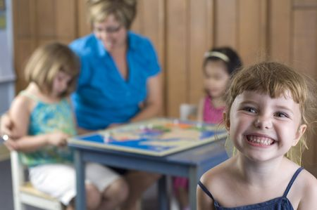 preschool: Children and teacher play and learn geography by using a puzzle map.