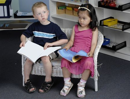 Preschool boy and girl read books during their class. photo