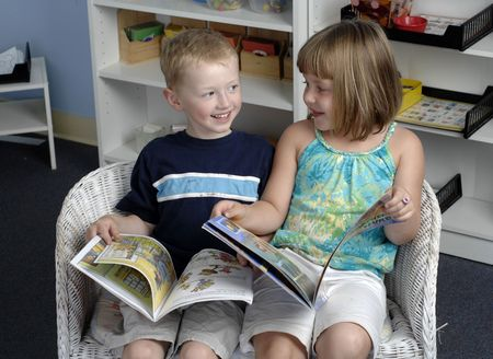 Preschool boy and girl read books during their class.