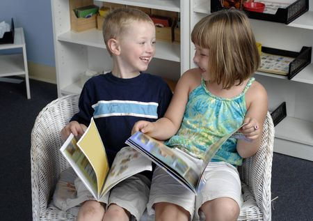 Preschool boy and girl read books during their class. photo