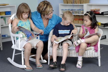 Teacher assists preschool boy and girls while they read books during their class.