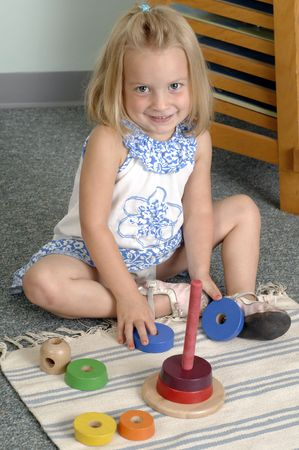 Girl learn while playing with different shapes  at the preschool class. photo