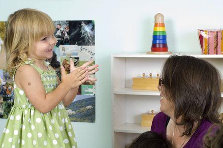 A cute blond girl interacts with her teacher at the preschool class.