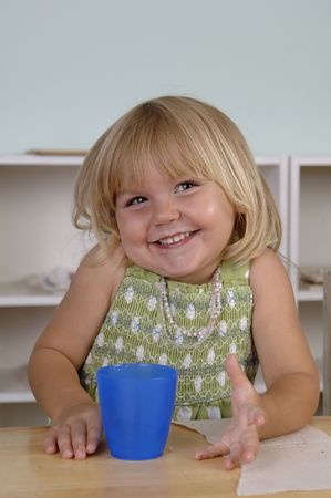 Young girl eats her snack during the break at her preschool classes. Stock Photo - 7346479