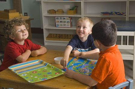 game board: Children have fun and learn while playing a board-game at the preschool class.