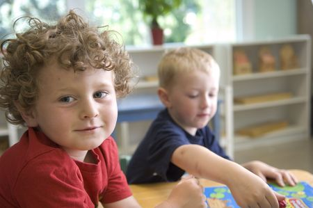 Children have fun and learn while playing a board-game at the preschool class. photo