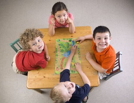 Children have fun and learn while playing a board-game at the preschool class.