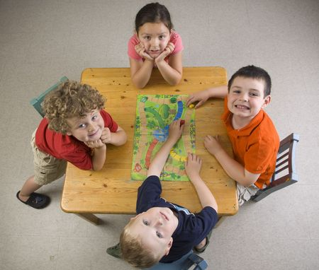 creativity: Children have fun and learn while playing a board-game at the preschool class.