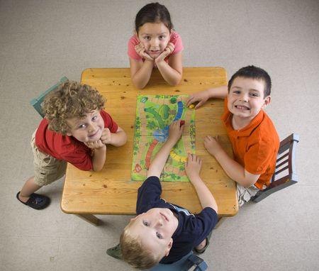 Los niños se diviertan y aprenden jugando un juego de mesa en la clase de preescolar.  Foto de archivo - 7415146
