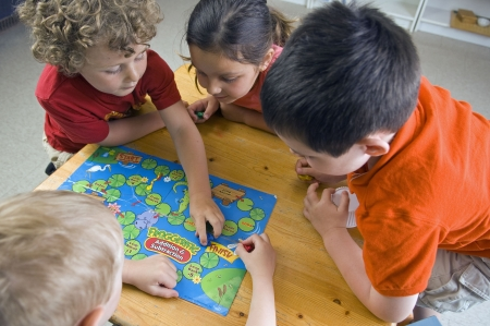 board: Children have fun and learn while playing a board-game at the preschool class.