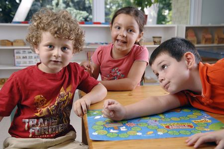 elementary age boy: Children have fun and learn while playing a board-game at the preschool class.