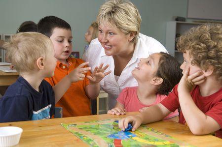 kinder: Los ni�os y maestros aprenden y jugar mientras juega un juego de mesa en la clase de preescolar.  Foto de archivo