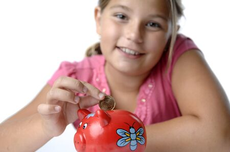 School girl count coins before dropping them into the piggy bank. Stok Fotoğraf - 7656720