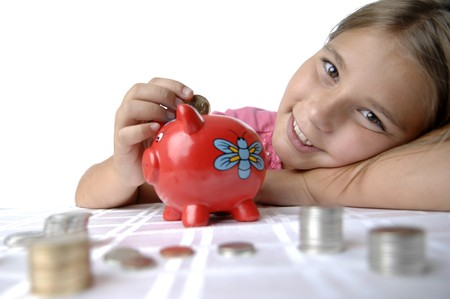 School girl count coins before dropping them into the piggy bank. Stockfoto
