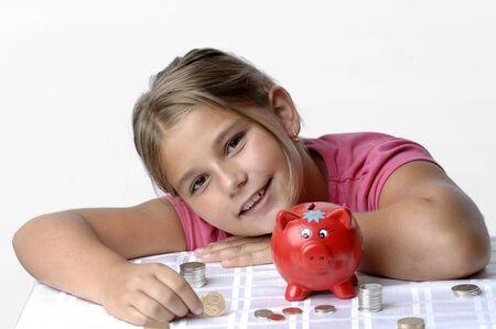 School girl count coins before dropping them into the piggy bank. Stock Photo