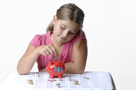 School girl count coins before dropping them into the piggy bank. Stok Fotoğraf - 7656745