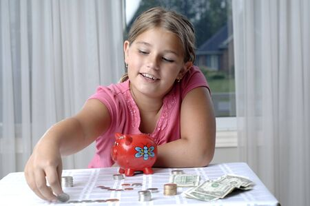 School girl count coins before dropping them into the piggy bank. Stok Fotoğraf
