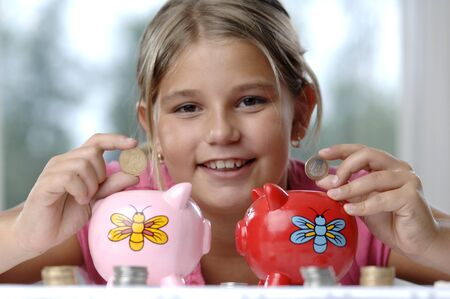 School girl count coins before dropping them into the piggy bank. Stok Fotoğraf - 7656789