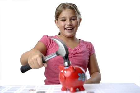 School girl is breaking her piggy bank with a hammer. Stock Photo