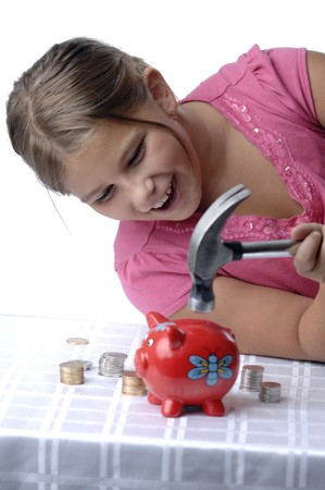 breaking: School girl is breaking her piggy bank with a hammer. Stock Photo