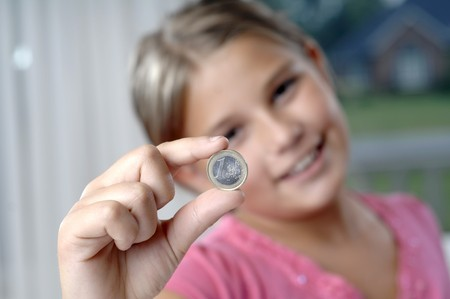 School girl is playing with a coin.