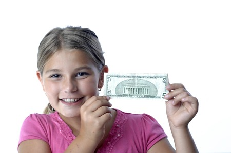 School girl is playing with a paper bills before putting them into the piggy bank.. Stock Photo - 7656748