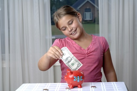 School girl is playing with a paper bills before putting them into the piggy bank.. Stok Fotoğraf - 7656826