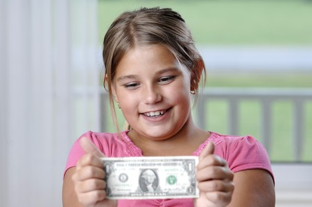 School girl is playing with a paper bills before putting them into the piggy bank.. Stock Photo