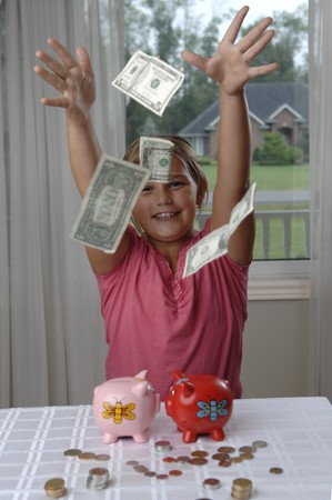 School girl is playing with a paper bills before putting them into the piggy bank.. photo