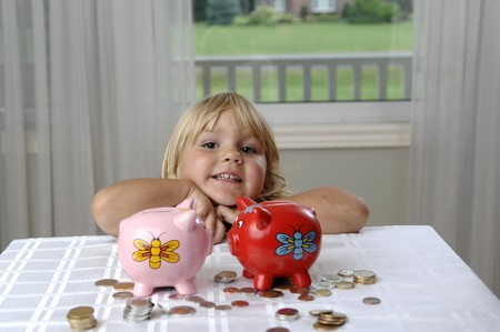 Little girl is looking at coins and piggy bank. Stock Photo