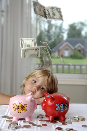 Money is falling around a little girl with piggy bank. photo
