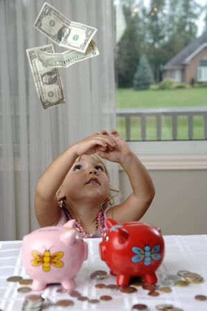 Money is falling around a little girl with piggy bank. Stock Photo