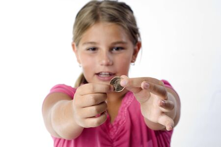 School girl is playing with a coin before dropping it into the piggy bank. Stock Photo