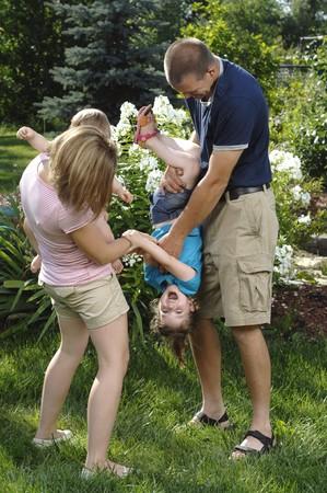 Giovane coppia gioca con i loro bambini nel cortile.