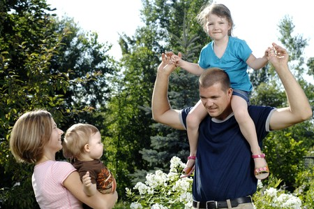 Young couple plays with their children in the backyard. photo