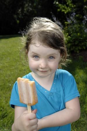 Cute girls eat ice cream in the garden.