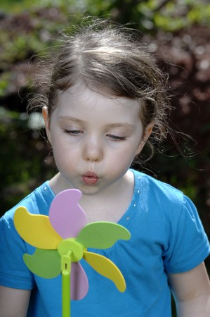 Cute girl blows at colorful spinner in the garden.