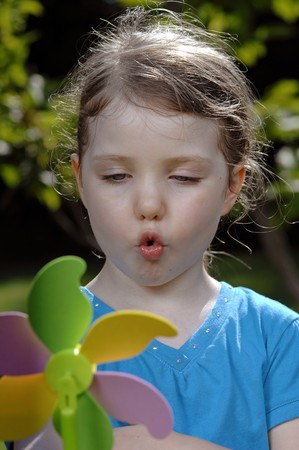 rotates: Cute girl blows at colorful spinner in the garden.