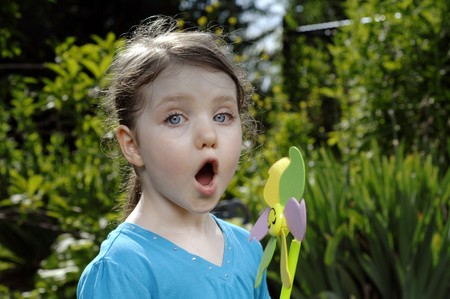 Cute girl blows at colorful spinner in the garden. Stock Photo - 7656984