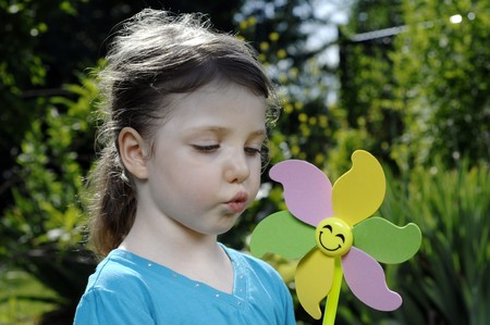 Cute girl blows at colorful spinner in the garden. Stock Photo - 7656972