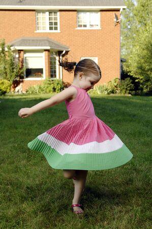 revolves: Little girls dances in the garden. Stock Photo