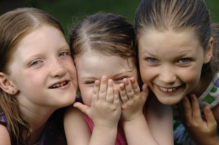 Three cute girls play in the garden.