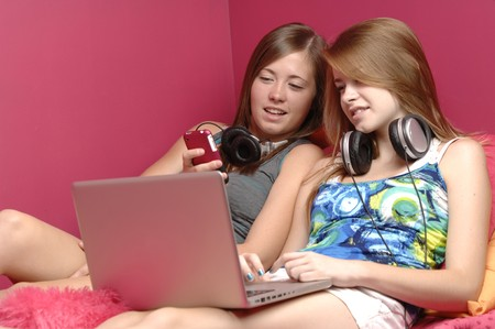 Teenage girls brows Internet on the laptop computer. Stock Photo